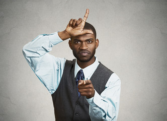 Bully boss executive man giving loser sign, grey wall background