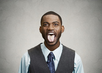 Man sticking his tongue out isolated grey wall background