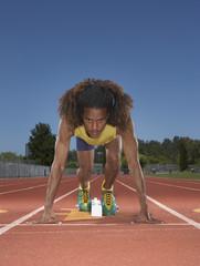 Male track runner preparing to race