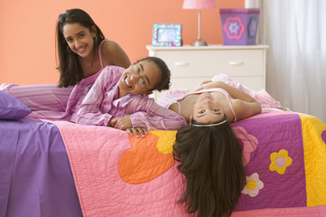 Three girls laying on bed