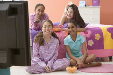Four girls in bedroom watching television and eating snacks