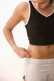 Teenager pinching fat on side of stomach