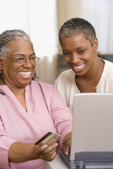 Mother and daughter with laptop and credit card