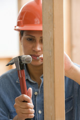 Female construction worker hammering nail into framework
