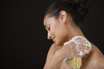 Close up profile of woman bathing with sponge