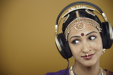 Indian woman in traditional dress listening to headphones