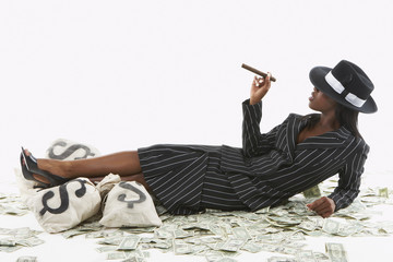 Businesswoman smoking a cigar by bags of cash