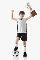 Young soccer player holding up trophy triumphantly