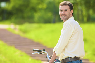 Portrait of Young Caucasian Handsome Walking with Bicycle