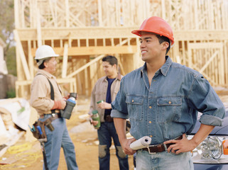 Manual worker holding blueprints on site