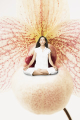 Young woman meditating in a giant flower
