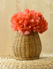Woven basket with red tissue paper flower