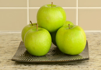 Green apples in flat square plate on counter top