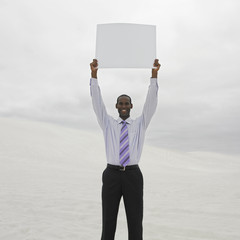 African businessman in the desert holding blank sign over his head