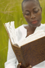 African American woman reading book outdoors