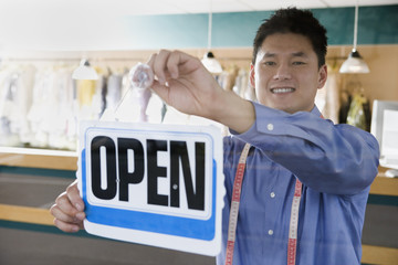 Asian drycleaner putting up open sign