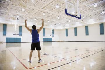 Man cheering on basketball court