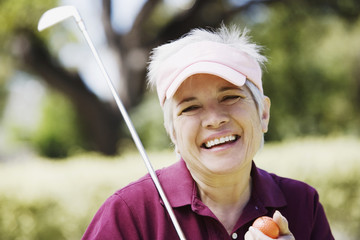 Middle-aged woman with golf club and golf ball