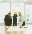 Businesspeople wearing hard hats and looking at blueprints in office