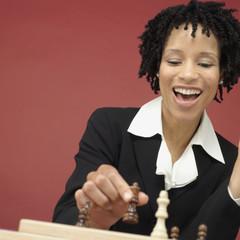 Studio shot of African woman playing chess