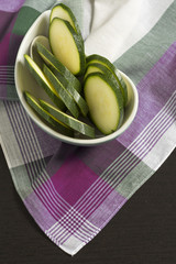Zucchini sliced ​​on Pink Scottish plaid tablecloth.