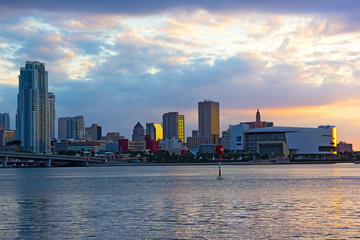 Panoramic sunset with bodies of water and city landmarks.