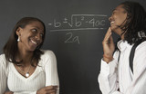 Fototapety Two African students next to math problem on blackboard
