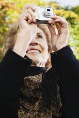 Senior woman taking photograph outdoors