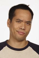 Close up studio shot of Asian man looking skeptical