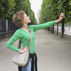 African woman taking own photograph outdoors