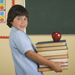 Boy carrying stack of books and apple in classroom
