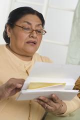 Senior Hispanic woman looking at mail