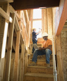 Construction worker with laptop sitting on unfinished stairway