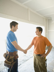 Male carpenters shaking hands inside construction site