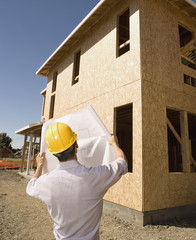 Rear view of architect reviewing blueprints near unfinished building
