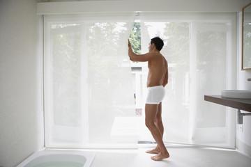 Man wearing underwear and looking out bathroom window