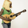 Studio shot of African woman wearing blonde wig and playing guitar
