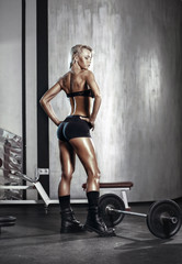fitness blonde girl posing with barbell in gym