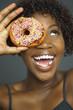 African woman holding doughnut over eye