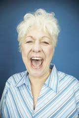 Studio shot of senior woman laughing