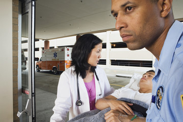 Paramedic and doctor wheeling man on gurney