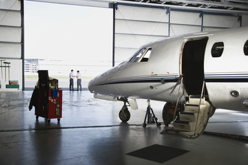 Airplane in hangar with men in background