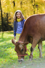 Autumn farm - girl and cow grazing grass