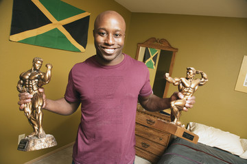 African man holding body building trophies