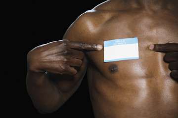 African man with Hello My Name Is sticker on bare chest