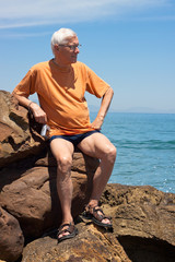 Senior tourist man on the rocky beach