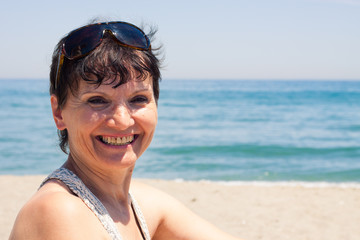 Happy middle aged woman on the beach