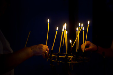 Hands lighting candles in a church