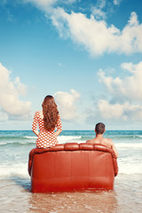 couple resting in leather couch on the beach