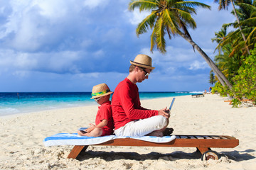 father and son with laptop on vacation
